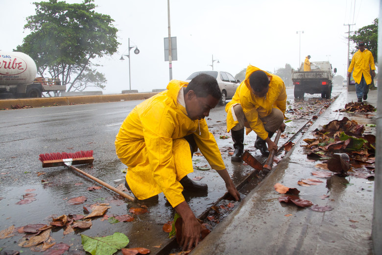 Workers clean highway gutters as Tropical Storm Erika approaches Santo Domingo, in the Dominican Republic, Friday, August 28, 2015. Tropical Storm Erika began to lose steam Friday over the Dominican Republic, but it left behind a trail of destruction that included several people killed on the small eastern Caribbean island of Dominica, authorities said. (AP Photo/Tatiana Fernandez)