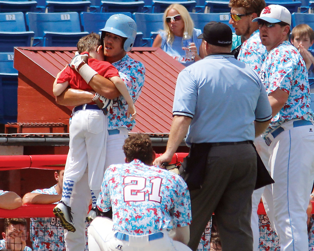 In this Aug. 1, 2015,  photo, Liberal's Gavin Wehby holds Bee Jays batboy Kaiser Carlile moments after the 9-year-old was accidentally hit in the head during a National Baseball Congress World Series game in Wichita, Kan. Kaiser, who was wearing a helmet, was struck by a follow-through swing near the on-deck circle. He died the following day. (Earl Watt/Leader & Times via AP) MANDATORY CREDIT