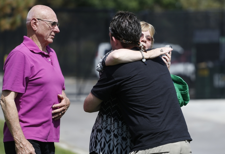 Sandy Phillips, right, whose daughter Jessica Ghawi was killed in the 2012 Aurora movie theater attack, hugs Eric McQuinn, brother of Matt McQuinn, who was killed in the Colorado movie theater shooting, as Phillips' husband Lonnie stands at left, after Colorado movie theater shooter James Holmes was formally sentenced, outside Arapahoe County District Court in Centennial, Colo., Wednesday, Aug. 26, 2015. Holmes was sentenced to multiple life sentences without parole for perpetrating the July 20, 2012 attack that left 12 dead and 70 wounded. (AP Photo/Brennan Linsley)