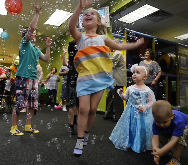 In this June 13, 2015 photo, Talia Pisano, second from right in blue dress, celebrates her second birthday with family and friends in Wheaton, Ill. Talia is receiving tough treatment for kidney cancer that spread to her brain at Lurie Children's Hospital in Chicago. She's also getting a chance at having babies of her own someday. To battle infertility sometimes caused by cancer treatment, some children's hospitals are trying a futuristic approach: removing and freezing immature ovary and testes tissue, with hopes of being able to put it back when patients reach adulthood and want to start families. (AP Photo/Christian K. Lee)