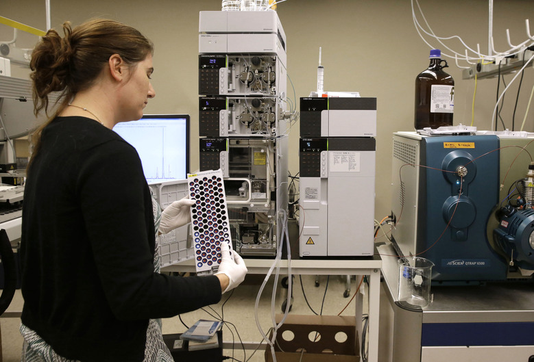 In this Aug. 10, 2015, photo, Christine Jelinek, a postdoctoral fellow at Johns Hopkins University, prepares to load a tray of vials containing cerebral spinal fluid into a liquid chromatograph in Baltimore. Dr. Akhilesh Pandey, a researcher at Johns Hopkins University, said his research analyzes both adult and fetal tissue, and by identifying which proteins are present, he can get clues that could be used to help detect cancer in adults earlier. (AP Photo/Patrick Semansky)