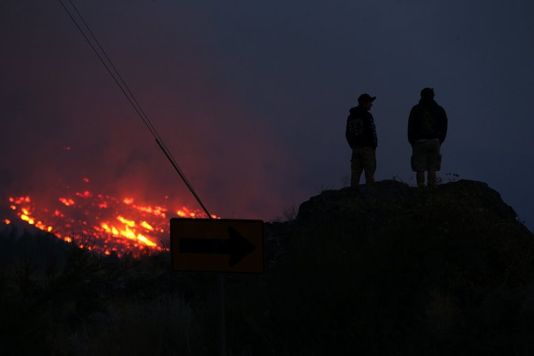 Cole Darwood, 16, left, and Jacob McMillan, 18, of Twisp, watch fires burn above the town early Thursday. (Erika Schultz/The Seattle Times)