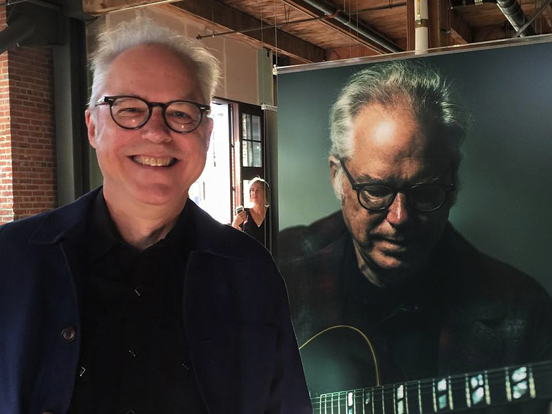 "Jazzman Bill Frisell stands with his portrait at the opening of ""Musician: A Portrait Project"" at Union Stables.  (Nicole Brodeur)"