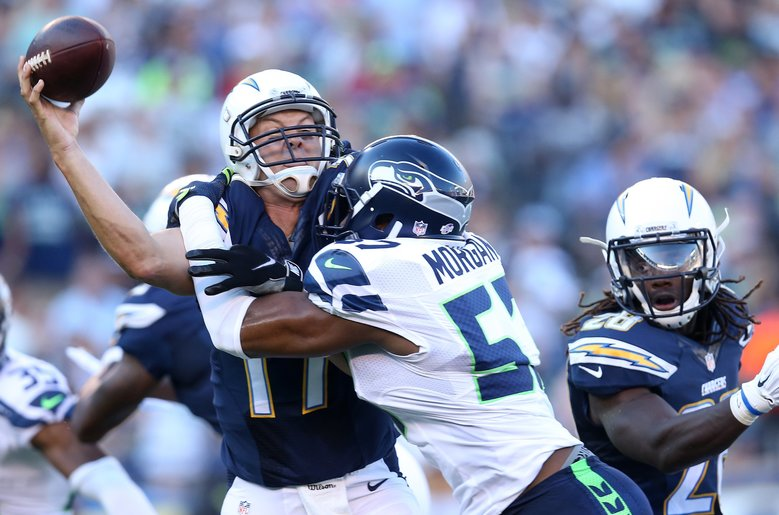 Seattle linebacker Mike Morgan (57) puts a hard hit on San Diego quarterback Philip Rivers. The Seattle defense had another strong showing in the exhibition game. (Stephen Dunn/Getty Images)