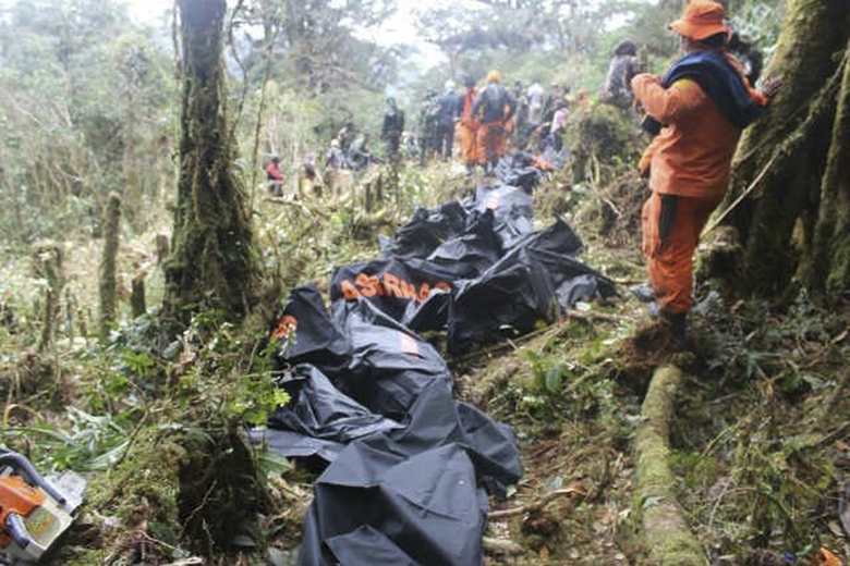 In this Aug. 18, 2015, photo provided by BASARNAS (National Search and Rescue Agency) rescuers work by the plane wreckage in Pegunungan Bintang, Papua province, Indonesia. Rescuers on Tuesday reached the site in eastern Indonesia where the Trigana Air Service passenger plane slammed into a mountain over the weekend, killing all 54 people on board, and found that the aircraft had been destroyed, officials said. (BASARNAS via AP)