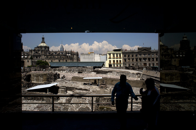 FILE – In this Friday, Aug. 7, 2015, file photo, a worker, standing in front of ongoing excavations at the Templo Mayor archeological site, directs people into the adjoining museum, in central Mexico City. Spanish conquistador Hernan Cortes conquered the Aztec capital Tenochtitlan in 1521, bringing to an end the empire that ruled over much of what is now Mexico. To root out the local religion, Cortes ordered temples destroyed, including the Templo Mayor, the giant step pyramid at the center of Aztec spiritual culture _ and site of their human sacrifices. The temple was leveled, and a Catholic church built over its remains _ though parts of the temple were uncovered in the 1970s, discovered in the digging of a metro in Mexico City. (AP Photo/Rebecca Blackwell, File)
