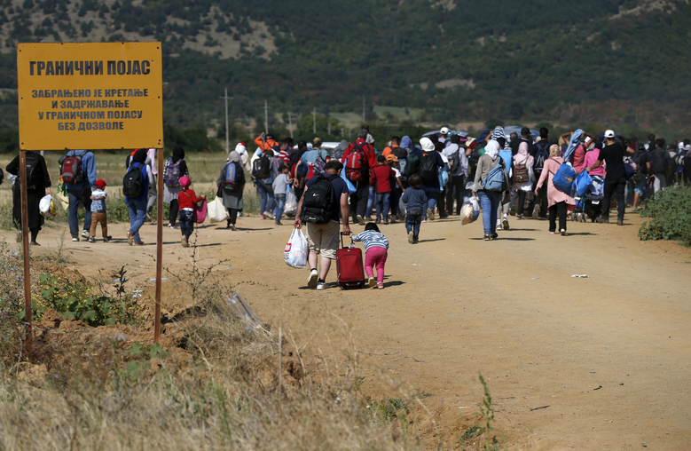 "Migrants walking from Macedonian border into Serbia, passing a Serbian border sign, near the village of Miratovac, Serbia, Monday, Aug. 24, 2015. The more than 5,000 migrants who reached Serbia overnight faced an overcrowded refugee center where they have to apply for asylum — the paper that allows them three days to reach Hungary. Serbian border sign says ""Border Area. No Tresspassing or Movement in the Border Without Permit."" (AP Photo/Darko Vojinovic)"