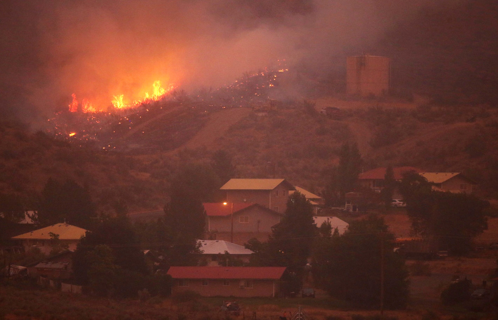 Flames are seen moving closer to houses north of Omak in a view from Highway 97.  (Bettina Hansen / The Seattle Times)