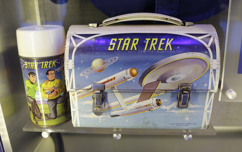 """In this Tuesday, July 21, 2015 photo, the lunch box astronaut Michael P. Anderson used as a child are among his personal effects displayed in the """"Forever Remembered"""" exhibit and memorial for the astronauts that perished on the Columbia and Challenger space shuttles, at the Kennedy Space Center Visitor Complex in Cape Canaveral, Fla. (AP Photo/John Raoux)"""