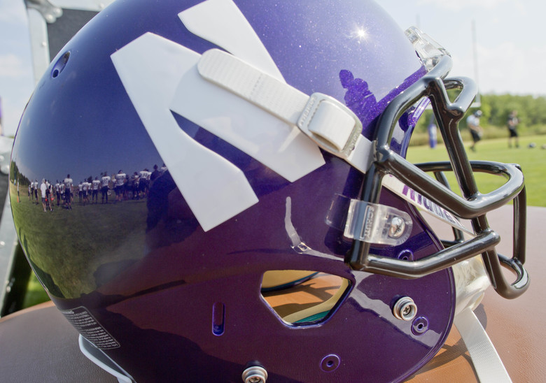 Northwestern football players are reflected in a helmet during drills at practice at the University of Wisconsin-Parkside campus on Monday, Aug. 17, 2015, in Kenosha, Wi. The National Labor Relations Board on Monday, Aug. 17, 2015, overturned a historic ruling that gave Northwestern University football players the go-ahead to form the nation's first college athletes' union, saying the prospect of union and non-union teams could throw off the competitive balance in college football. (AP Photo/Jeffrey Phelps)