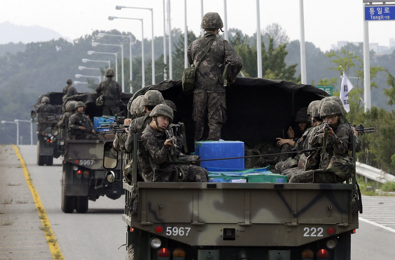 South Korean army soldiers ride on trucks in Paju, south of the demilitarized zone that divides the two Koreas, South Korea, Monday, Aug. 24, 2015. Marathon negotiations by senior officials from the Koreas stretched into a third day on Monday as the rivals tried to pull back from the brink. South Korea's military, meanwhile, said North Korea continued to prepare for a fight, moving unusual numbers of troops, hovercraft and submarines to the border. (AP Photo/Ahn Young-joon)