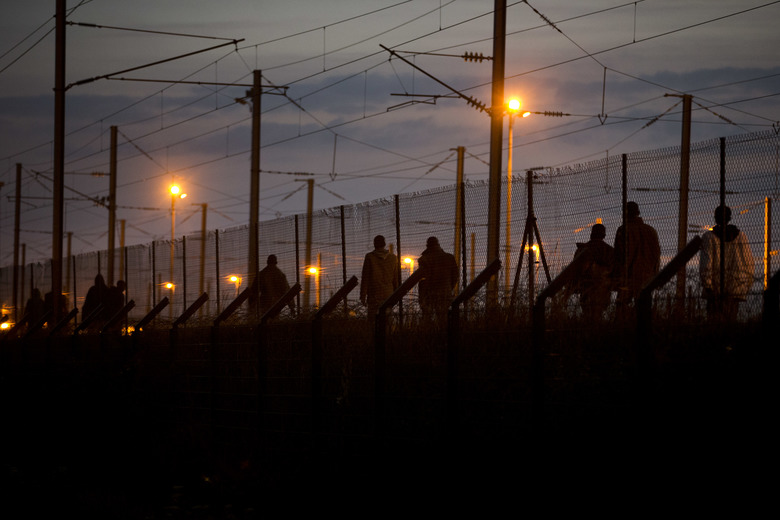 FILE – In this Monday, Aug. 3, 2015 file photo, migrants walk after crossing a fence as they attempt to access the Channel Tunnel, in Calais, northern France. (AP Photo/Emilio Morenatti, File)