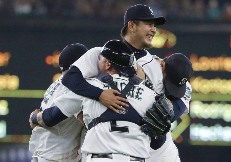 Seattle Mariners starting pitcher Hisashi Iwakuma, center, is mobbed by teammates, including catcher Jesus Sucre (2), after Iwakuma threw a no-hitter against the Baltimore Orioles in a baseball game Wednesday, Aug. 12, 2015, in Seattle. The Mariners won 3-0. (AP Photo/Ted S. Warren)