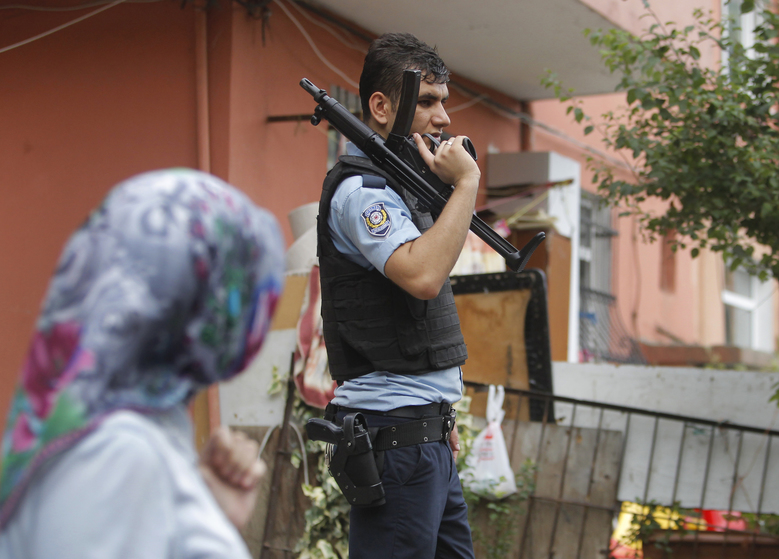 A woman walks past an armed Turkish police officer securing a road leading to the U.S. Consulate building in Istanbul, Monday, Aug. 10, 2015. Two assailants opened fire at the building on Monday, touching off a gunfight with police before fleeing the scene, Turkish media reports said. (AP Photo/Lefteris Pitarakis)