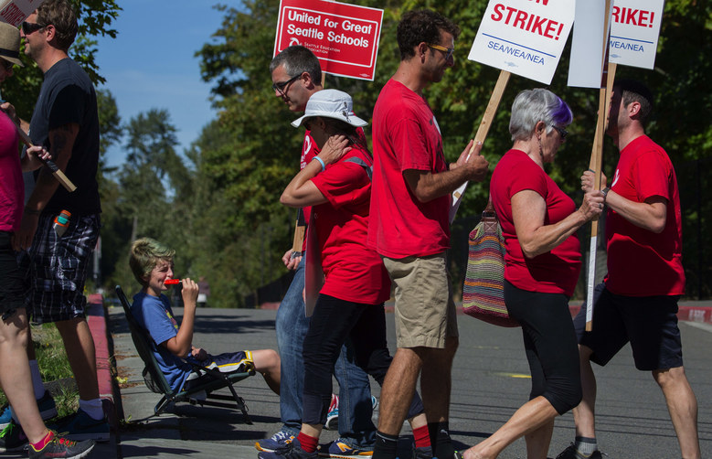 Twelve-year-old Dante Golash, enjoys a popsicle as Chief Sealth High School teachers picket on the sidewalk in front of him in front of Chief Sealth High School in West Seattle Wednesday afternoon, September 9, 2015.  Dante's father Ian is a world history and social studies teacher at the school.  (Ellen M. Banner / The Seattle Times)