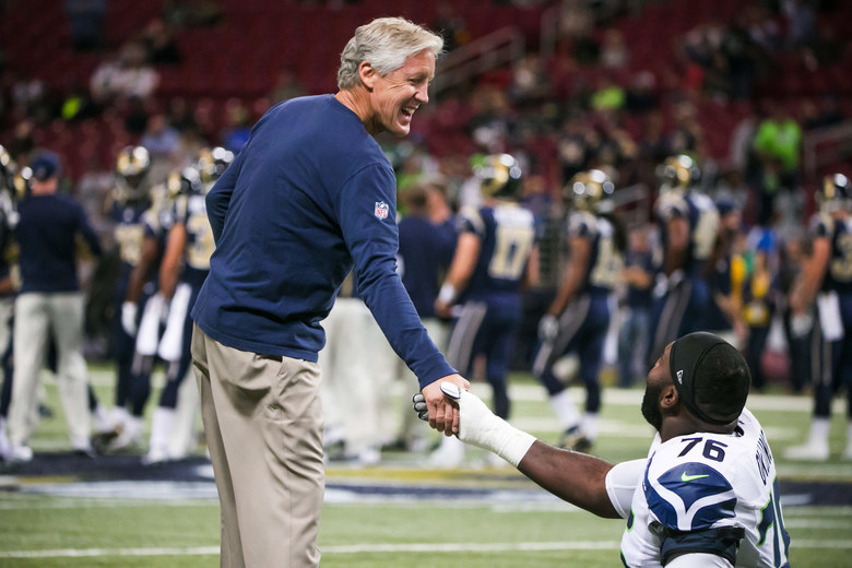 Seahawks Head Coach Pete Carroll shakes hands with offensive lineman Russell Okung before the Seattle Seahawks take on the St. Louis Rams. (Bettina Hansen / The Seattle Times)