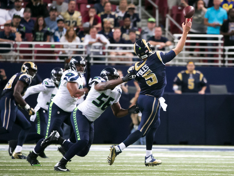 Seahawks defensive lineman Cliff Avril pressures Rams quarterback Nick Foles into throwing the ball away, leading to fourth down and a field goal kick for the Rams to pull ahead 34-31 in overtime during their game Sept. 13 in St. Louis. (Bettina Hansen / The Seattle Times)