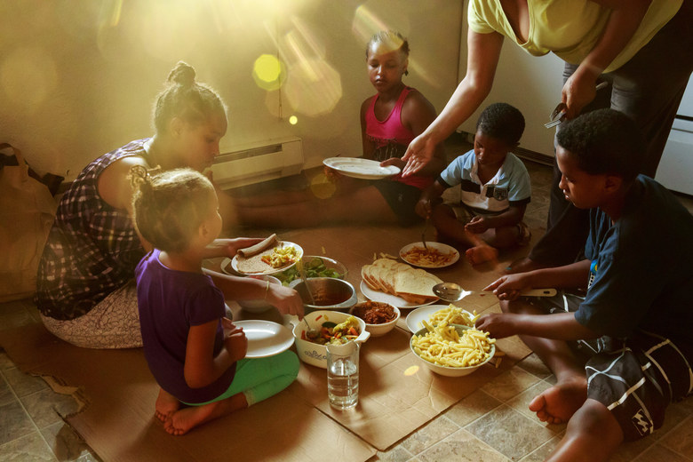 Emebet Amdetsion serves her five children dinner on the floor of their sparsely furnished town house while her husband Wondimu Habtemariam attends ESL classes. The family, diversity visa immigrants from Ethiopia, previously lived in a homeless shelter. (Erika Schultz / The Seattle Times)