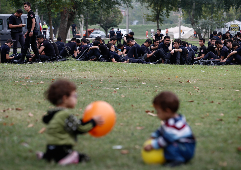 Syrian refugee children play in the foreground as Turkish police officers sit in a stadium used for traditional Kirkpinar oil wrestling, as migrants and refugees wait to cross into Europe near Turkey's western border with Greece and Bulgaria, in Edirne, Turkey, Wednesday, Sept. 23, 2015. Hundreds of migrants have made the trek to Edirne in the hope of being allowed to cross into neighboring Greece or Bulgaria and avoid the often-risky journey across the Aegean Sea. Many arrived last week but have been blocked from approaching the border by law enforcement. (AP Photo/Emrah Gurel)