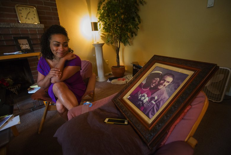 Tiffany Prinos admires her parents' wedding photo in her mother's SeaTac apartment. Her mother died recently, and Prinos came from her home in Missouri to pack up her mom's belongings. (Ellen M. Banner/The Seattle Times)