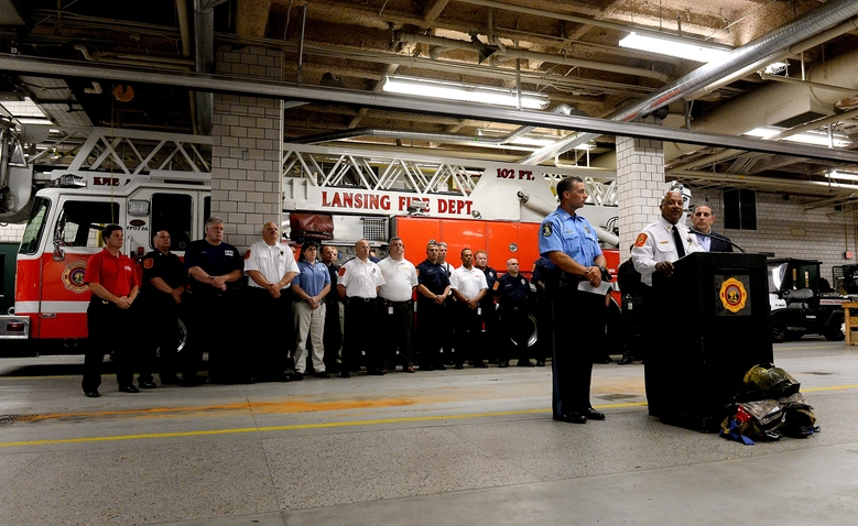 Lansing firefighters line up behind Fire Chief Randy Talifarro, Police Chief Mike Yankowski and Mayor Virg Bernero as they speak during a press conference Wednesday, Sept. 9, 2015 in Lansing, Mich. Dennis Rodeman, a 35-year-old Lansing firefighter has died after being struck by a hit-and-run driver as he collected money for charity. (Dave Wasinger/Lansing State Journal via AP)  NO SALES; MANDATORY CREDIT