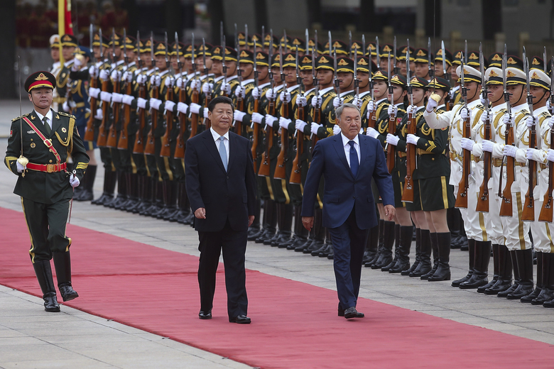 FILE – In this Monday, Aug. 31, 2015 file photo, Chinese President Xi Jinping, center, accompanies Kazakhstan President Nursultan Nazarbayev, right,  to view an honor guard during a welcoming ceremony outside the Great Hall of the People, in Beijing. Russian leader Vladimir Putin, South Korean President Park Geun-hye and U.N. Secretary General Ban Ki-moon shine at the top of China's guest list at this week's grand commemorations of the 70th anniversary of Japan's defeat in World War II, but high-level representatives from Western democracies are largely absent. (Lintao Zhang/Pool Photo via AP, File)