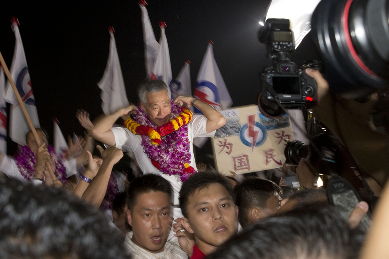 Singapore's Prime Minister Lee Hsien Loong of the ruling People's Action Party celebrates a win in his constituency in Singapore, Saturday, Sept. 12, 2015. The party that has ruled Singapore since it became a country a half-century ago appeared poised to stay in power for five more years as the city-state's citizens voted Friday in a compulsory election. (AP Photo/Ng Han Guan)