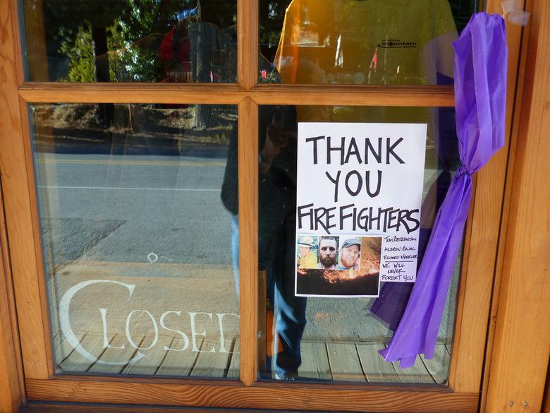 In the window of Winthrop Mountain Sports, a sign and a purple ribbon express appreciation for fallen firefighters. (Brian J. Cantwell / The Seattle Times)