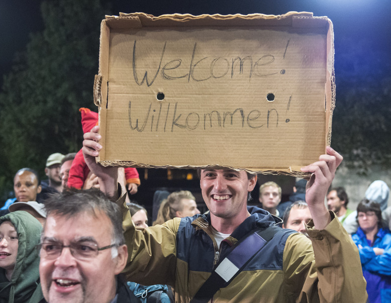 "FILE – In this Saturday, Sept. 5, 2015 file photo, a man holds a ""Welcome"" sign during the arrival of refugees at the train station in Saalfeld, central Germany. Hundreds of refugees arrived in a train from Munich to be transported by busses to an accomodation center. The United States and the European Union project themselves as models for the world when it comes to democracy and human rights. Yet a common issue, migration, is bitterly dividing each of them(AP Photo/Jens Meyer, File)"