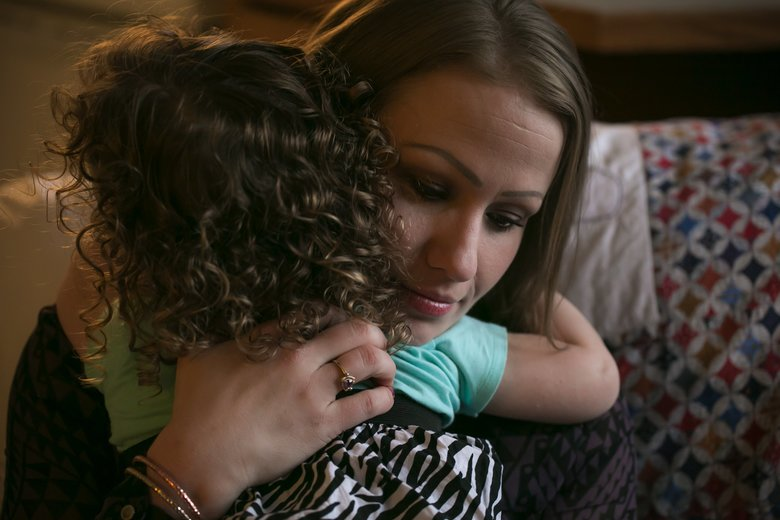 Dana Disharoon hugs one of her three daughters; they were living in temporary housing in Magnuson Park. (Bettina Hansen / The Seattle Times)