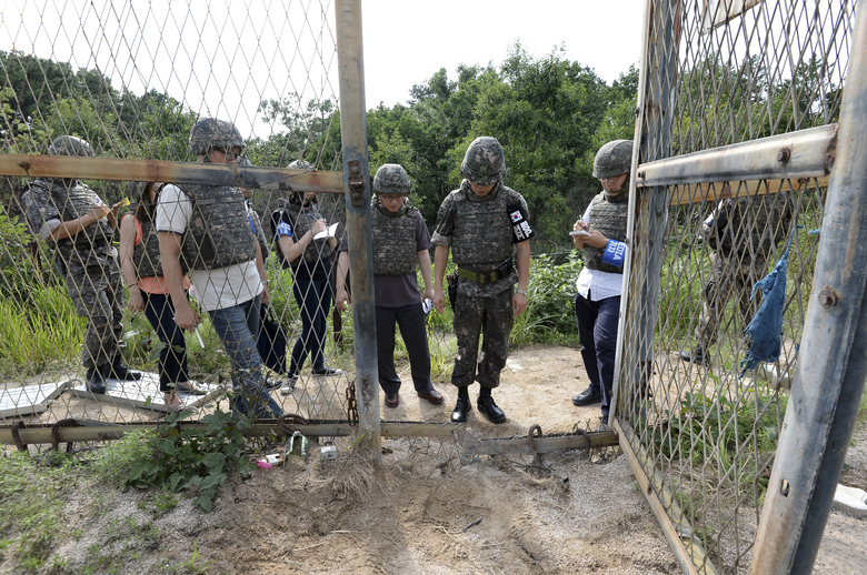 """FILE – In this Aug. 9, 2015 file photo provided by the Defense Ministry, an unidentified South Korean army official, second from right, gives a briefing to the media at the scene of a blast inside the demilitarized zone in Paju, South Korea. North Korea insisted Tuesday, Sept. 1, 2015 that its recent expression of """"regret"""" over a mine explosion that maimed two South Korean soldiers was not an apology, as Seoul claims it was. (The Defense Ministry via AP, FIle)"""