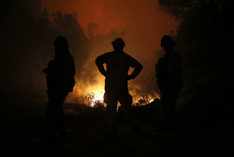Firefighters watch as the flames of the Butte Fire approach a containment line near San Andreas, Calif.,  Friday Sept. 11, 2015.(AP Photo/Rich Pedroncelli)