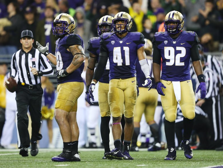 Husky defense, including Washington defensive tackle Taniela Tupou, from left, outside linebacker Cory Littleton, back, linebacker Travis Feeney and defensive lineman Jaylen Johnson react as officials determine that Oregon wide receiver Bralon Addison, who ran the 4th and 1 play as quarterback, picked up a first down.  (Lindsey Wasson/The Seattle Times)