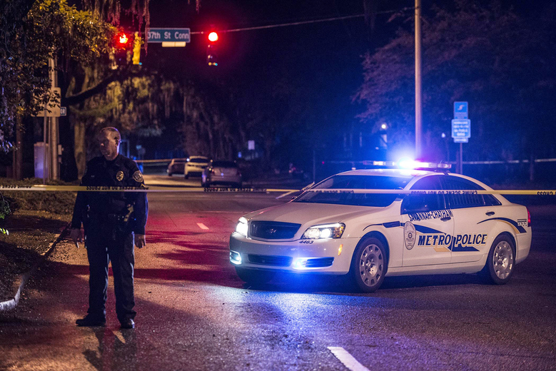 A police fficer stands in front of his car early Wednesday morning, Oct. 28, 2015, after a shooting in Savannah, Ga. Authorities are investigating after they say two Savannah-Chatham Metropolitan Police officers and a third person were shot. Police spokeswoman Eunicia Baker says both officers suffered non-life-threatening injuries. (Josh Galemore/Savannah Morning News via AP)