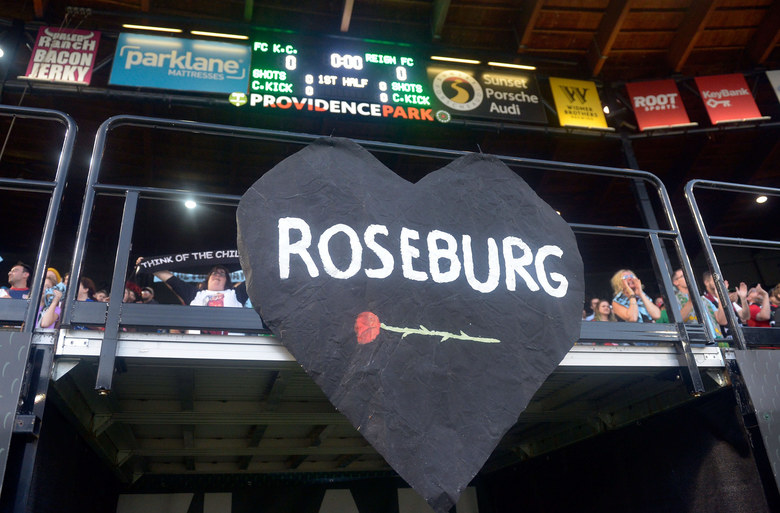 A sign honoring the victims of the shooting in Roseburg, Ore., hangs in the stands during the NWSL final between the Seattle Reign FC and the FC Kansas City in Portland, Ore.