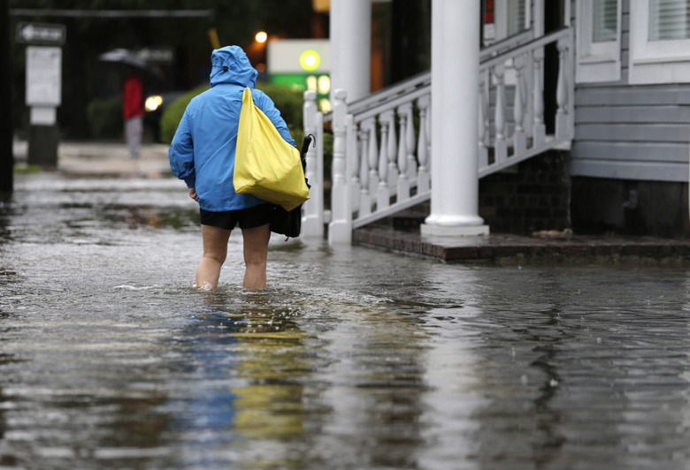 A woman walks down a flooded sidewalk toward an open convenience store in Charleston, S.C., Sunday, Oct. 4, 2015. President Barack Obama declared a state of emergency in South Carolina and ordered federal aid to bolster state and local efforts as flood warnings remained in effect for many parts of the East Coast through Sunday. (AP Photo/Chuck Burton)