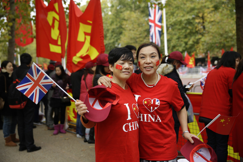 People wearing I love China t-shirts pose for a photograph as they wait to see Chinese President Xi Jinping and his wife Peng Liyuan pass by in a carriage ride along the Mall to Buckingham Palace in London, Tuesday, Oct. 20, 2015. Chinese President Xi Jinping arrived in Britain Monday for a four-day state visit as part of a push to increase trade ties between the two countries. (AP Photo/Matt Dunham)