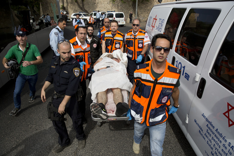 Israeli medics carry a wounded person at the scene of a shooting attack in Jerusalem, Tuesday, Oct. 13, 2015. A pair of Palestinian men boarded a bus in Jerusalem and began shooting and stabbing passengers, while another assailant rammed a car into a bus station before stabbing bystanders, in near-simultaneous attacks that escalated a month long wave of violence. Two Israelis and one attacker were killed. (AP Photo/Oded Balilty)