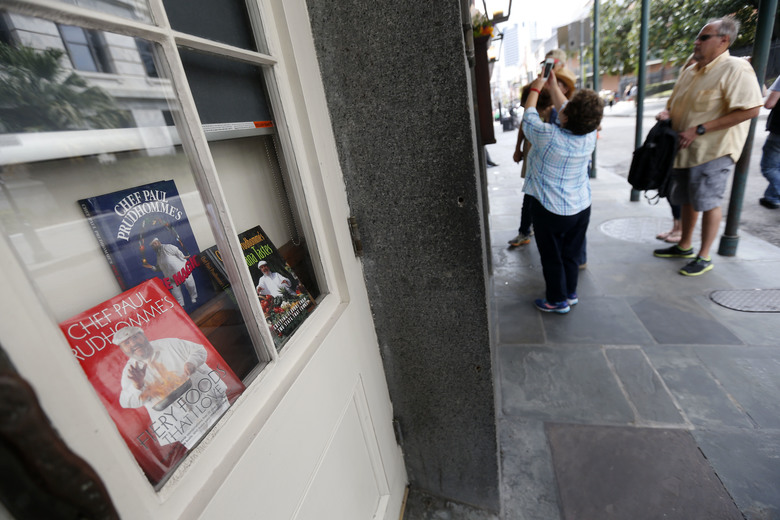 People take photos of flowers placed outside K-Paul's Louisiana Kitchen in the French Quarter of New Orleans, Thursday, Oct. 8, 2015. The proprietor, famed New Orleans Chef Paul Prudhomme, passed away Thursday. He was 75. (AP Photo/Gerald Herbert)