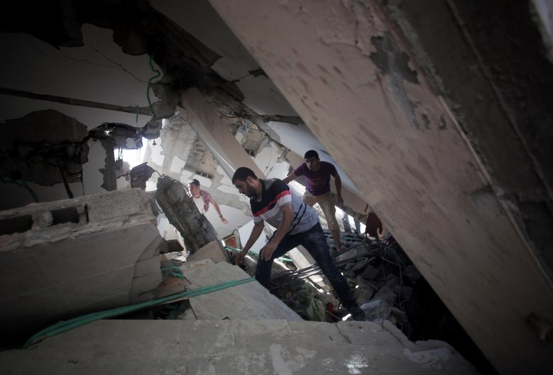 Palestinians search for survivors under the rubble of a house destroyed by an Israeli missile strike, in Gaza City, July 21, 2014. (Khalil Hamra/The Associated Press)