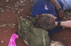 In this photo released by West Australia Police media unit, a West Australia Tactical Response Unit officer tends to Reginald George Foggerdy after he was found in an area about 170km east of Laverton, Western Australia, Monday, Oct. 13, 2015. Foggerdy had been on a hunting trip with a family member near Lake Ransom Road, when he went missing on October 7, 2015.(Glen Roberts/WA Police via AP)