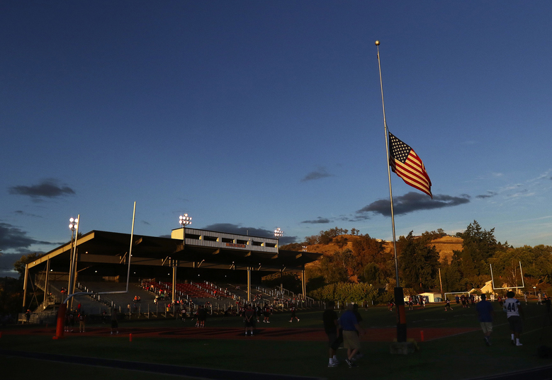 The U.S. flag flies at half-staff at Roseburg High School as the football team warms up for its game Oct. 9. Three of the shooting victims were recent graduates of Roseburg High. (Michael Sullivan / Special to The Seattle Times)
