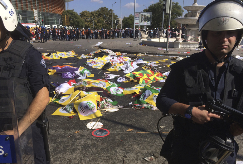Bodies of victims are covered with flags and banners as police officers secure the area after an explosion in Ankara, Turkey, Saturday, Oct. 10, 2015. Two bomb explosions apparently targeting a peace rally in Turkey's capital Ankara on Saturday has killed many people  a news agency and witnesses said. The explosions occurred minutes apart near Ankara's train station as people gathered for the rally organized by the country's public sector workers' trade union. (AP Photo/Burhan Ozbilici)