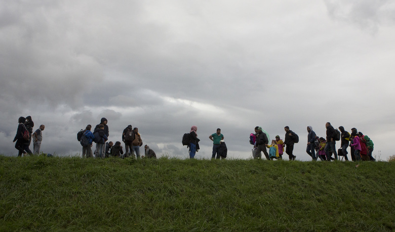 Migrants walk on a dyke after crossing from Croatia, in Brezice, Slovenia Monday, Oct. 19, 2015. Croatia's interior minister has rejected Slovenia's accusations that Croatia broke an agreement on limiting the numbers crossing their border to 2,500 a day, saying the Slovenes have kept changing the figure. (AP Photo/Darko Bandic)