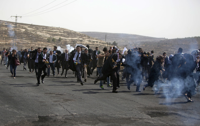 Palestinian lawyers run from tear gas fired by Israeli troops during a demonstration by scores of Palestinian lawyers called for by the Palestinian Bar Association in solidarity with protesters at the Al-Aqsa mosque compound in Jerusalem's Old City, near Ramallah, West Bank, Monday, Oct. 12, 2015. In recent weeks, at least 25 Palestinians, including nine attackers, have been killed by Israeli forces, while five Israelis have been killed in attacks. (AP Photo/Majdi Mohammed)