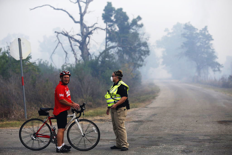 Cyclist Lance McInnes, from Austin, talks to a Texas Alcoholic Beverage Commission agent wearing a face mask to protect herself from the smoke of the Hidden Pines Fire, at a roadblock at Park Road 1C and Alum Creek Road, near Smithville, Texas, Thursday, Oct. 15, 2015. (Rodolfo Gonzalez /Austin American-Statesman via AP)  AUSTIN CHRONICLE OUT, COMMUNITY IMPACT OUT, INTERNET AND TV MUST CREDIT PHOTOGRAPHER AND STATESMAN.COM, MAGS OUT; MANDATORY CREDIT