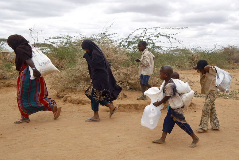 "FILE– In this Friday Aug. 5 2011 file photo,  newly arrived Somali family carry their supply of aid outside Dadaab, eastern Kenya, 100 kms (60 miles) from the Somali border. Calamitous famines appear to have vanished from the planet, but more must be done to eradicate all such scourges, including redrafting U.S. terror legislation that inhibits life-saving humanitarian work, according to a new report. The study, part of the 2015 Global Hunger Index published Monday, Oct. 12, 2015 says it's one of the ""unheralded achievements"" of the last 50 years: the elimination of calamitous famines that cause more than 1 million deaths, and reduction ""almost to a vanishing point"" of great famines, which cause more than 100,000 deaths. (AP Photo/ Jerome Delay-File)"