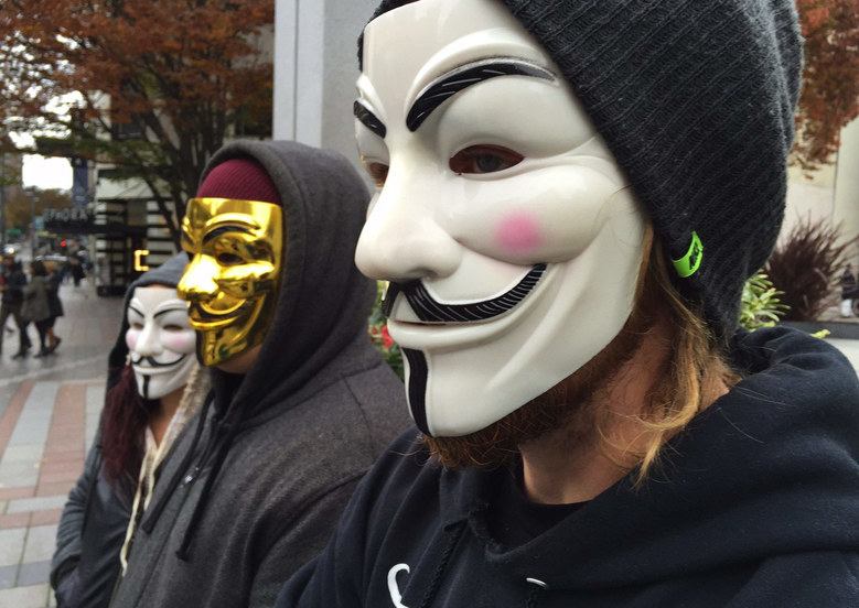 Protesters gather at Westlake Park on Guy Fawkes Day. All three masks were purchased from Amazon for $6 each using the Amazon Prime account of gold mask's mom.  (Alan Berner / The Seattle Times)