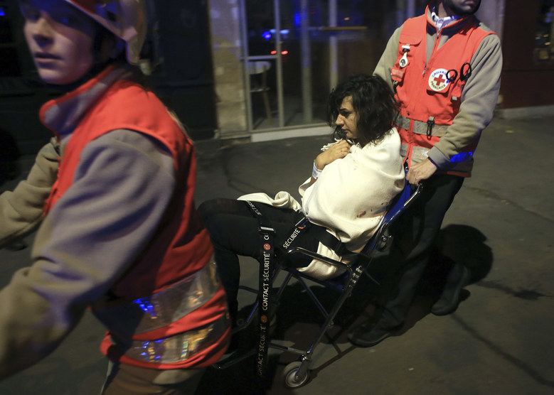 A woman is being evacuated from the Bataclan theater after a shooting in Paris.  French President Francois Hollande declared a state of emergency and announced that he was closing the country's borders. (AP Photo/Thibault Camus)