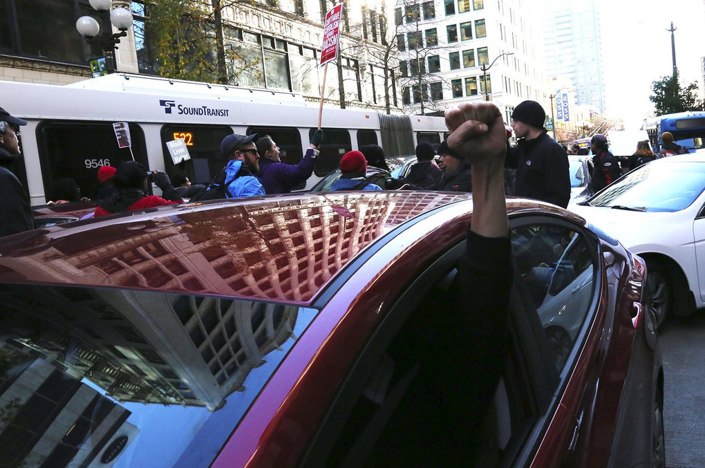 Though blocked by Black Lives Matter protesters in the street, a driver signals solidarity with the demonstration.  (Alan Berner / The Seattle Times)